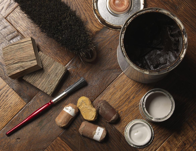 Wood flooring care items on a dark wood floor